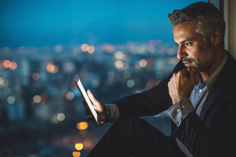 Hombre adulto mirando una tablet y tocandose la barbilla