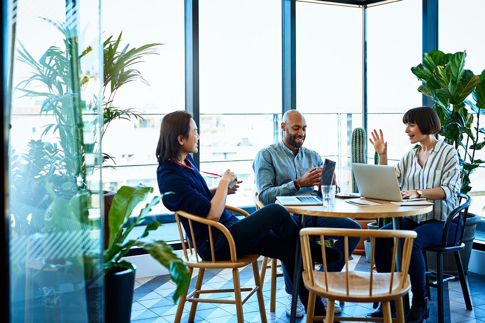 Tres personas en una mesa conversando