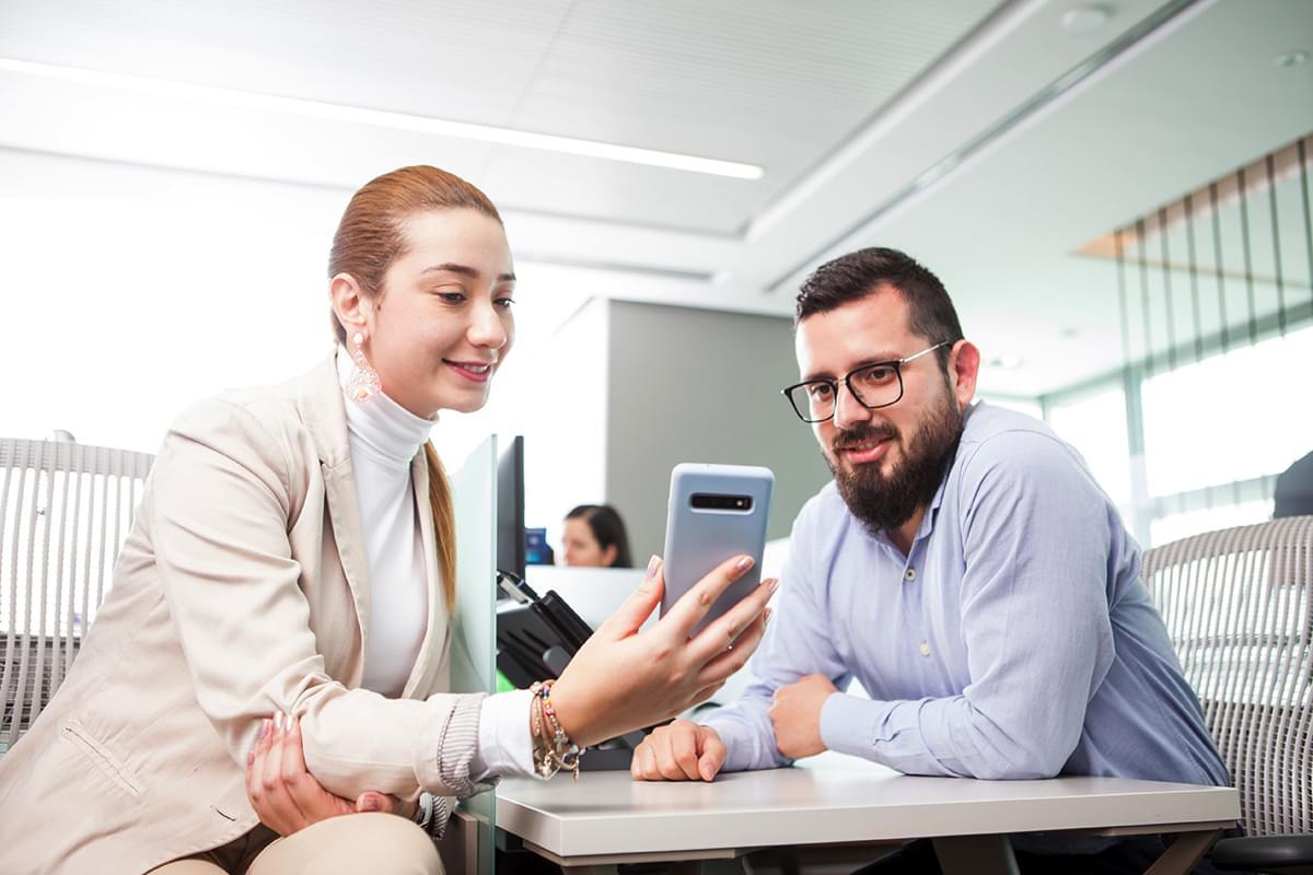 hombre y mujer sentados juntos y mirando un celular