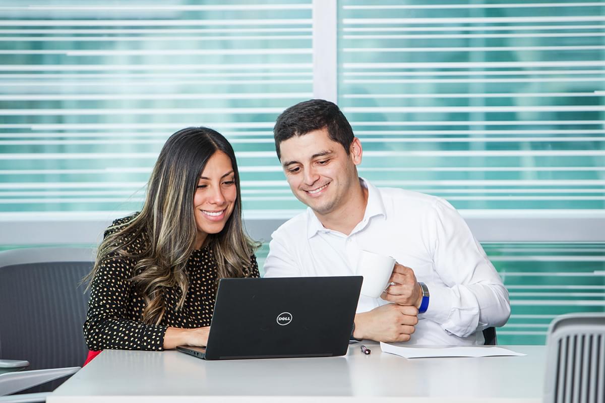 hombre y mujer sentados juntos y mirando un notebook