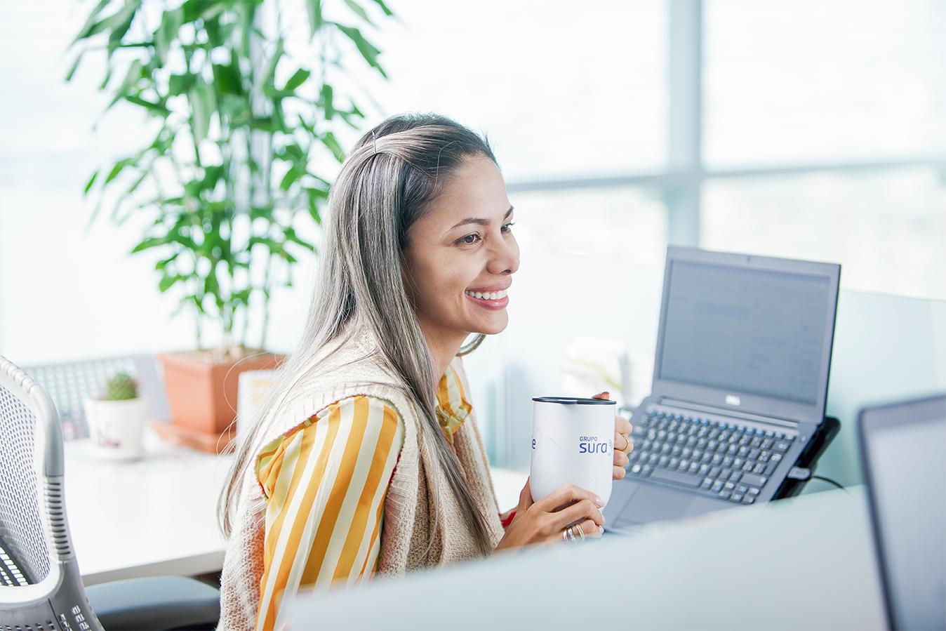 mujer en escritorio frente pantallas y teclado